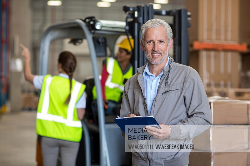 Portrait of warehouse manager holding a clipboard in warehouse