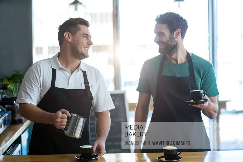 Smiling waiter interacting while making cup of coffee at counter in cafA?