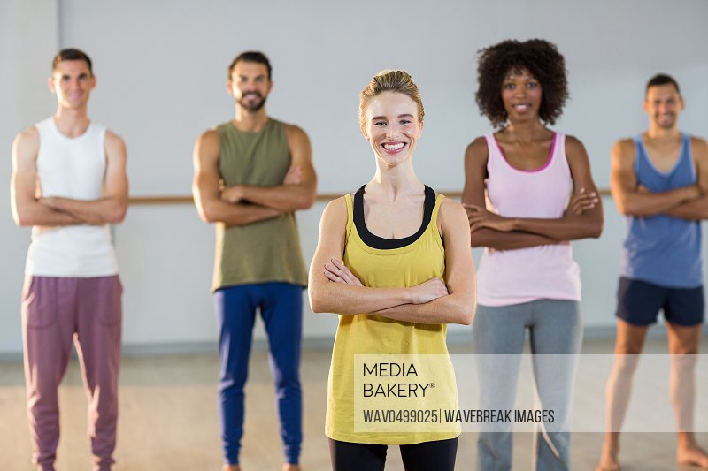Portrait of group of people with arms crossed standing in fitness studio