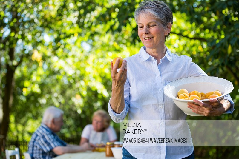 Senior woman holding a bowl of apricot in garden on a sunny day