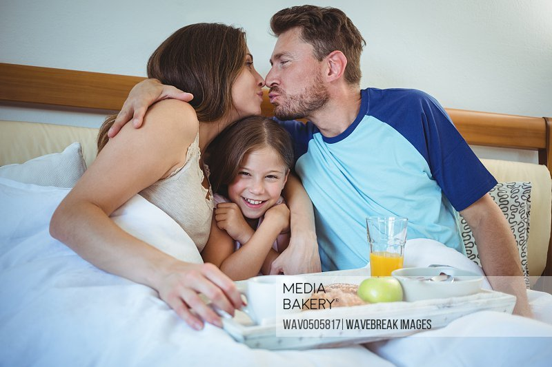Parents kissing while sitting on bed with daughter and having breakfast at home