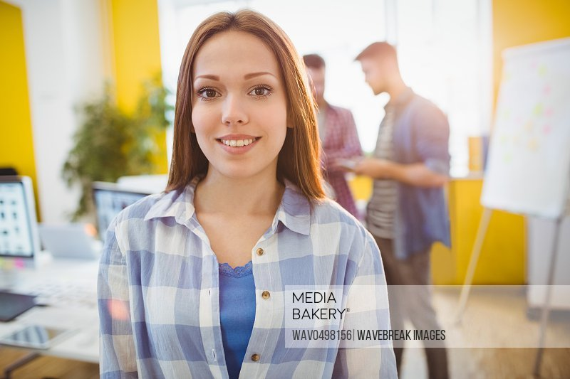 Portrait of smiling businesswoman standing against coworkers in creative office