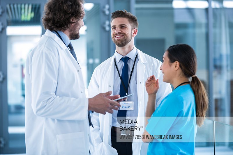 Doctor holding digital tablet having a discussion with colleagues