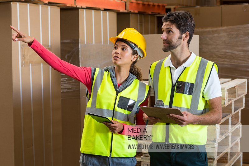 Warehouse workers discussing with clipboard and digital tablet in warehouse