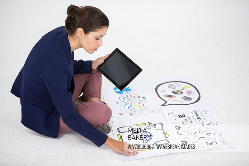 Businesswoman using digital tablet while working on icon charts against white background