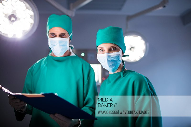 Portrait of male and female surgeon holding a medical report
