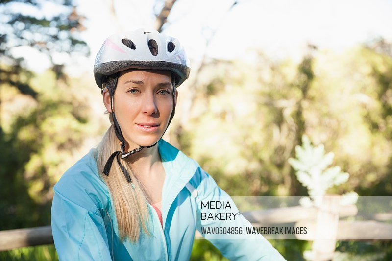 Portrait of female mountain biker in the forest on a sunny day
