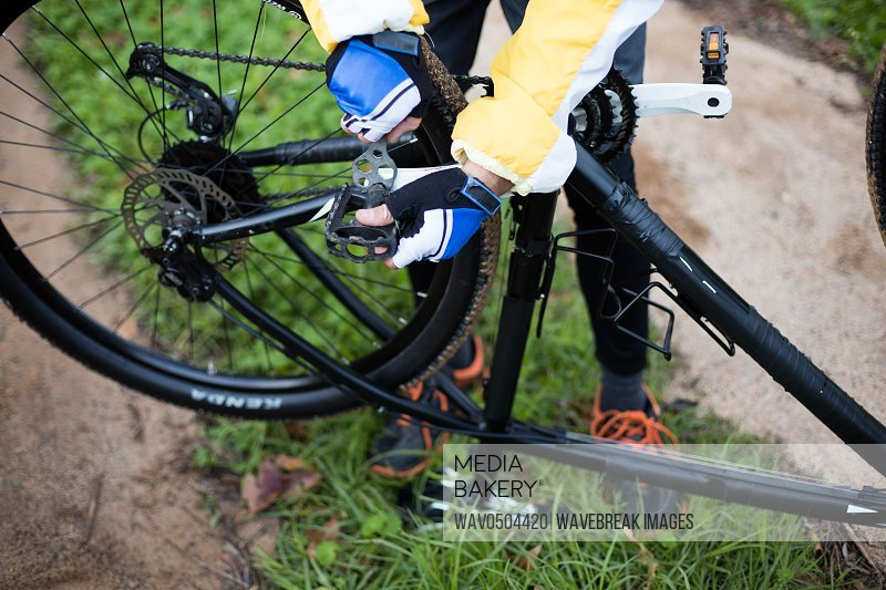 Low section of male biker repairing mountain bike in countryside