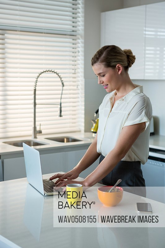 Woman using laptop while having breakfast in kitchen at home