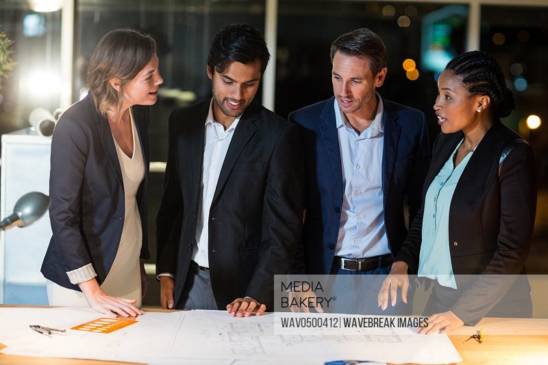 Group of businesspeople discussing over blueprint in the office