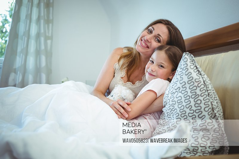 Mother lying with daughter on bed at home
