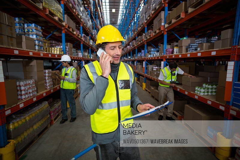 Warehouse worker talking on mobile phone and holding clipboard in warehouse
