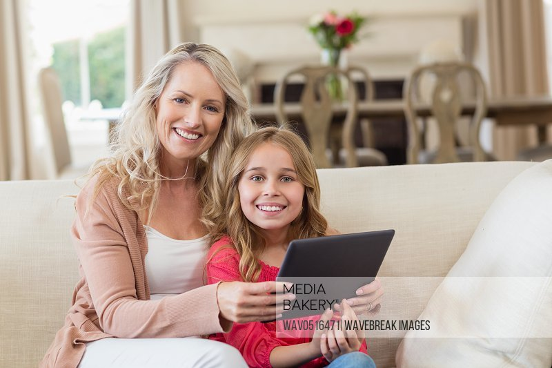 Mother and daughter using digital tablet at home