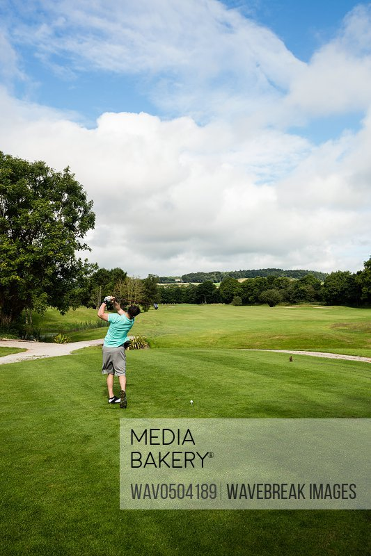 Rear view of man playing golf in golf course