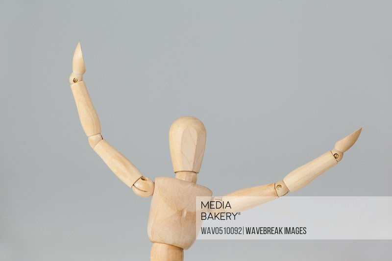 Wooden figurine with arms spread wide against grey background