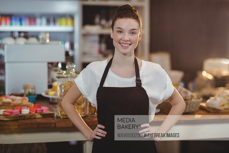 Portrait of smiling waitress standing with hands on hip in cafe