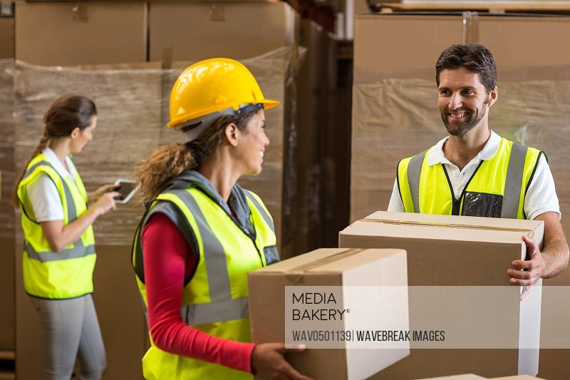 Smiling warehouse workers carrying a cardboard box in warehouse