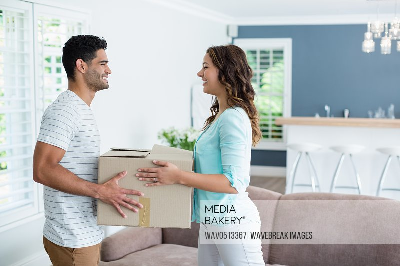 Couple holding card boxes in living room