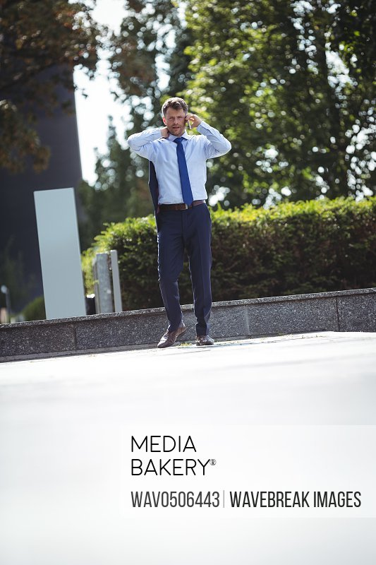 Handsome businessman talking on mobile phone while walking on road