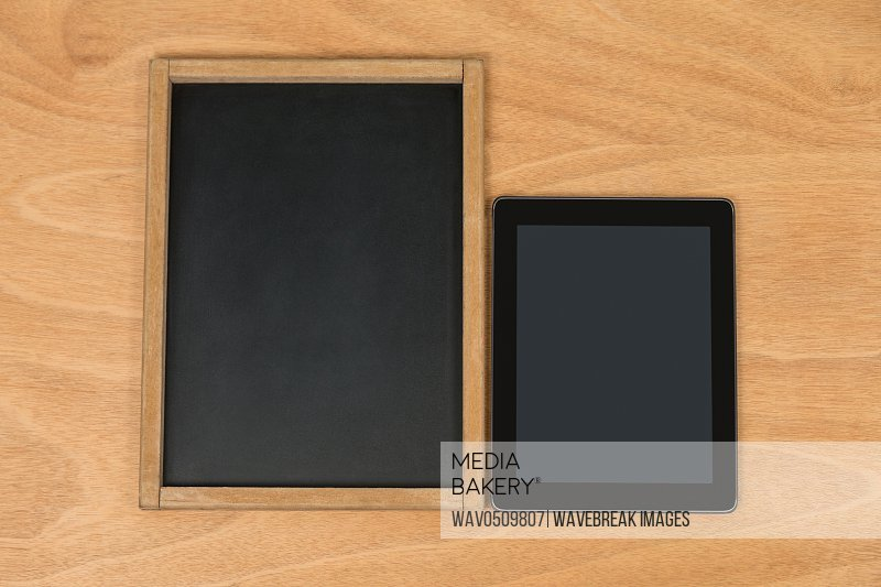 Close-up of old chalk board and digital tablet on wooden background