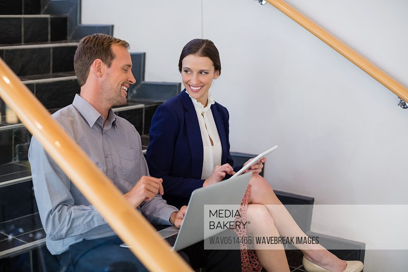 Businessman and woman sitting on steps using laptop