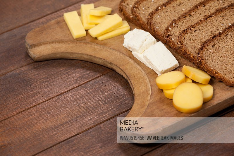 Slices of brown bread and variety of cheese on wooden chopping board