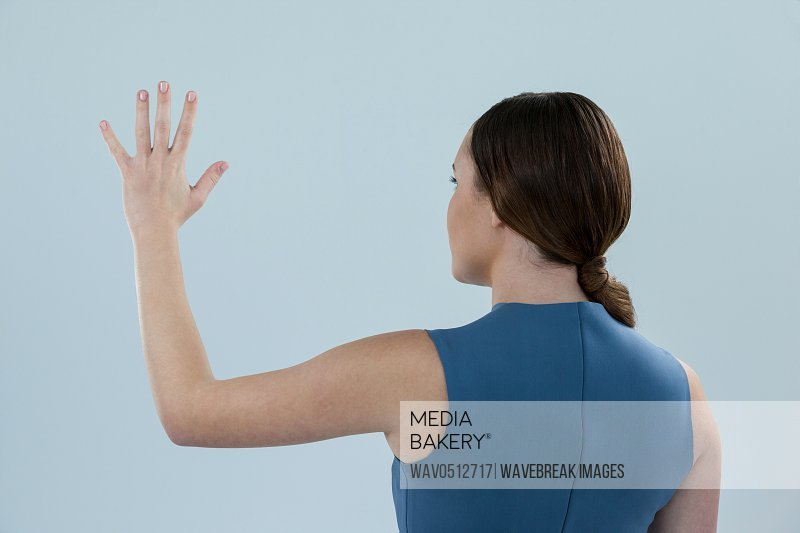 Beautiful woman pretending to touch an invisible screen against grey background