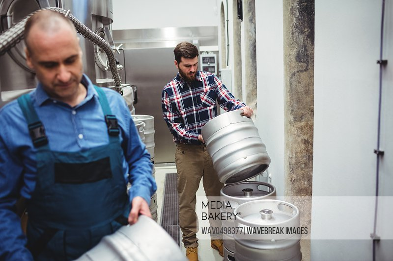 Manufacturer and worker carrying kegs at brweery