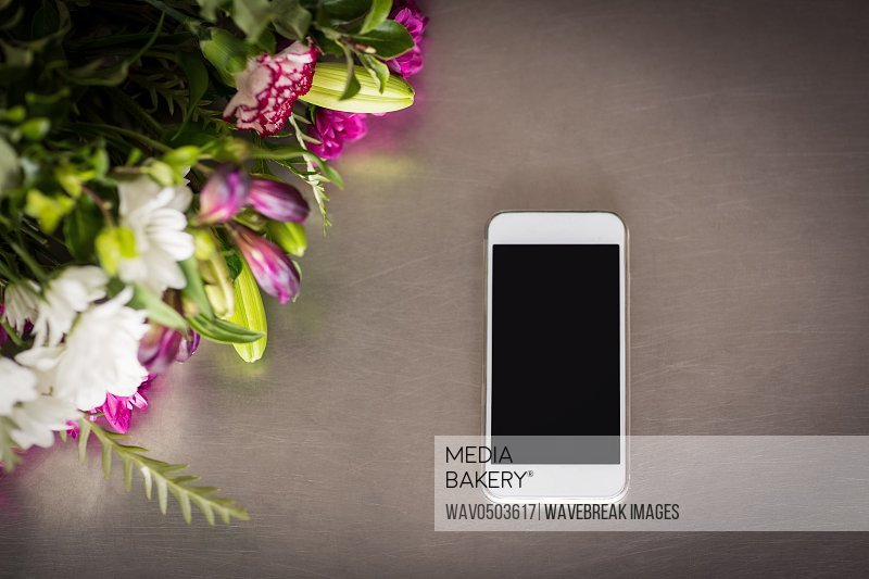 Flowers and mobile phone on the table at florist shop
