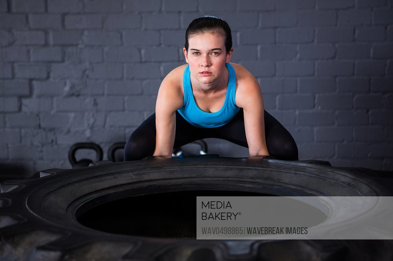 Portrait of serious female athlete picking up tire while exercising in gym