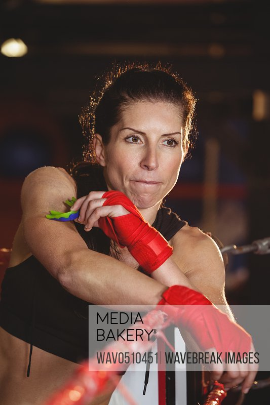 Thoughtful female boxer sitting in the ring at fitness studio