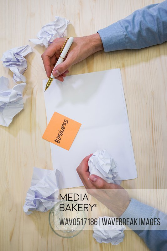 Graphic designer writing business on sticky note