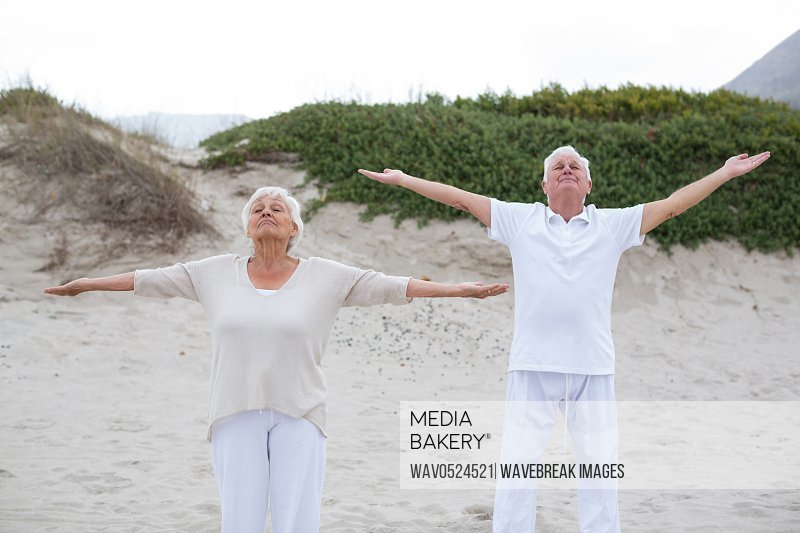 Senior couple standing with arms outstretched