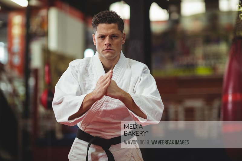 Portrait of karate player performing karate stance in fitness studio