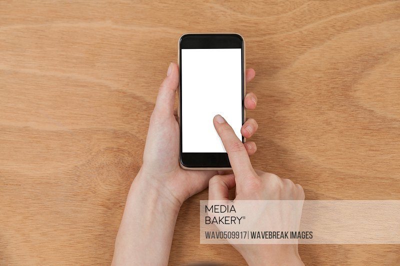 Close-up of hands using mobile phone against wooden background