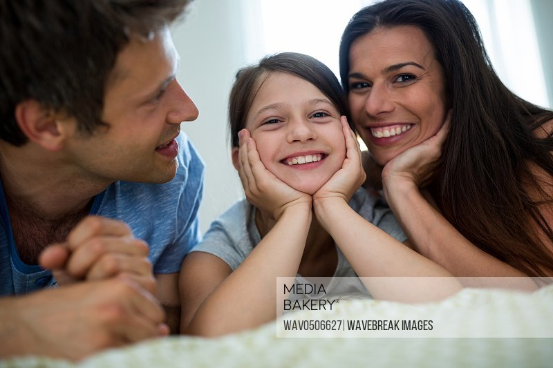 Happy parents and daughter lying in bedroom at home