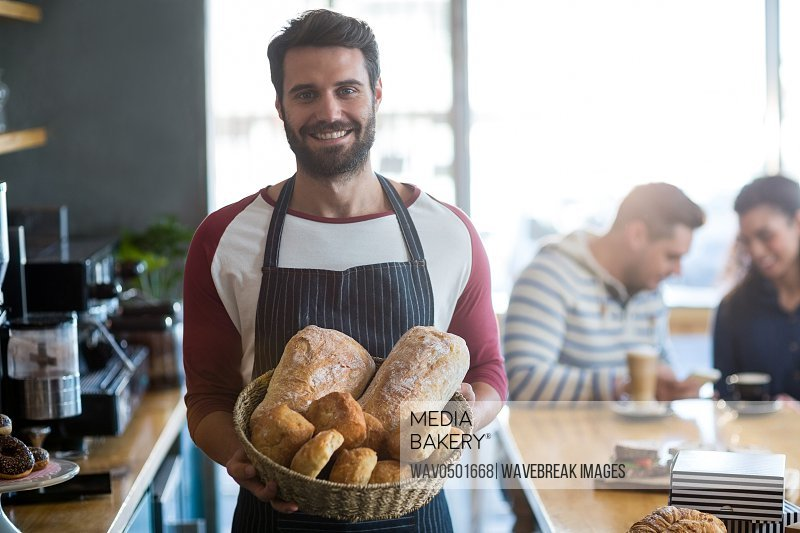 Portrait of smiling waiter holding a basket of bread in cafA?