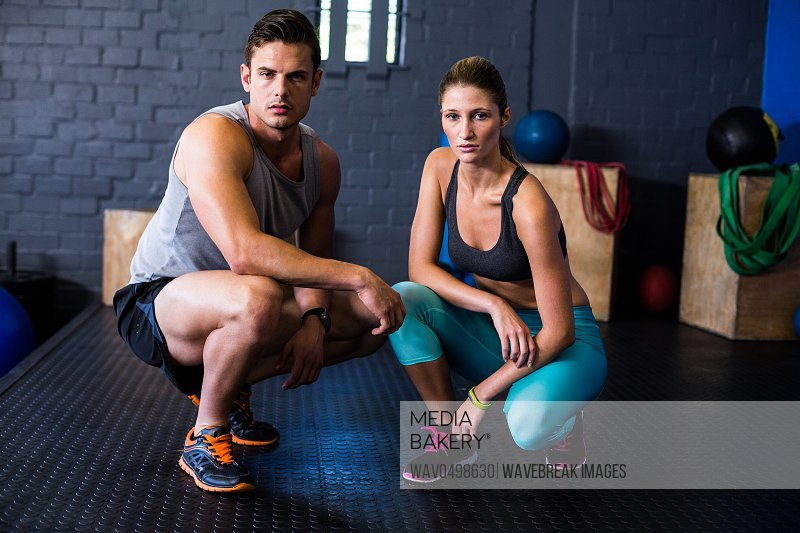 Portrait of confident male and female athletes crouching in fitness studio