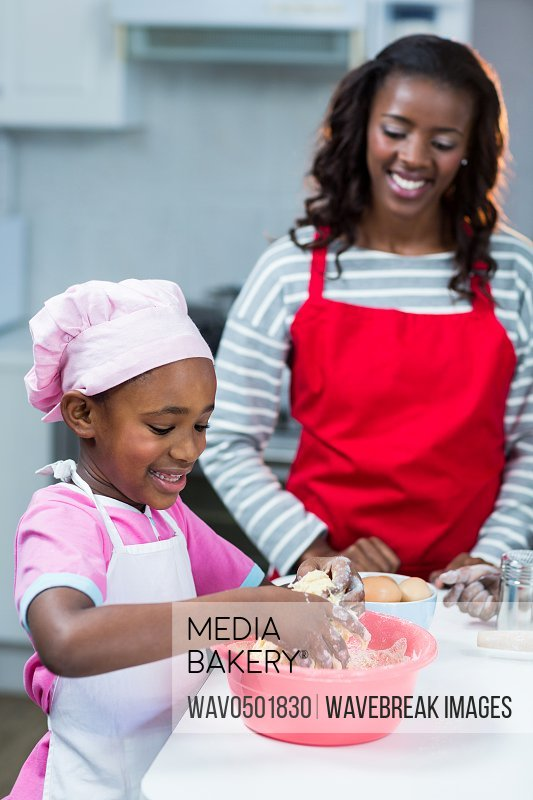 Girl preparing cake with mother in kitchen