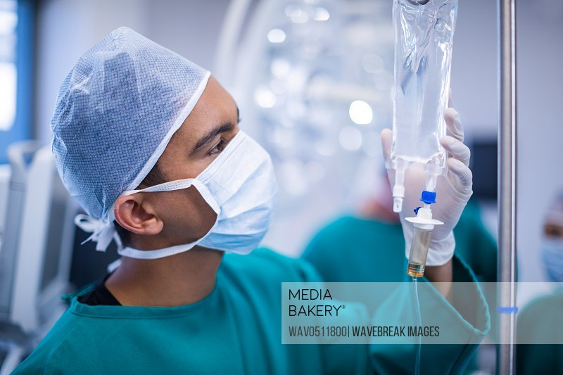Surgeons adjusting iv drip in operation theater of hospital