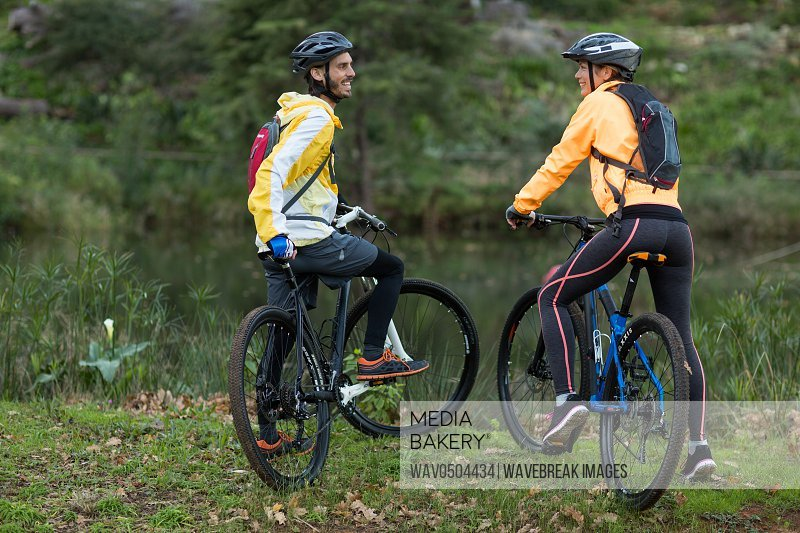 Biker couple interacting with each other with mountain bike in countryside