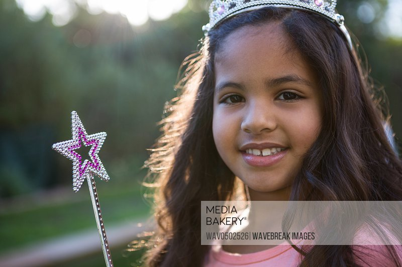 Portrait of happy girl in tiara and wand at the garden