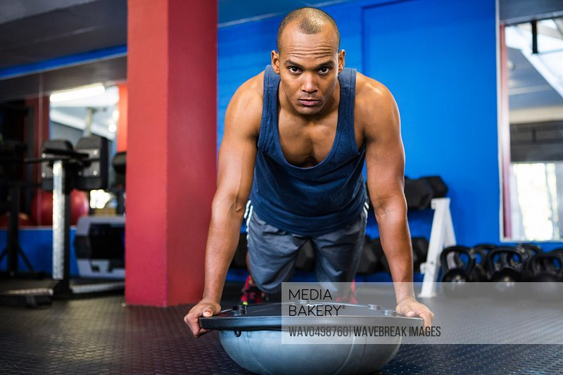 Portrait of serious male athlete with BOSU ball while exercising in gym