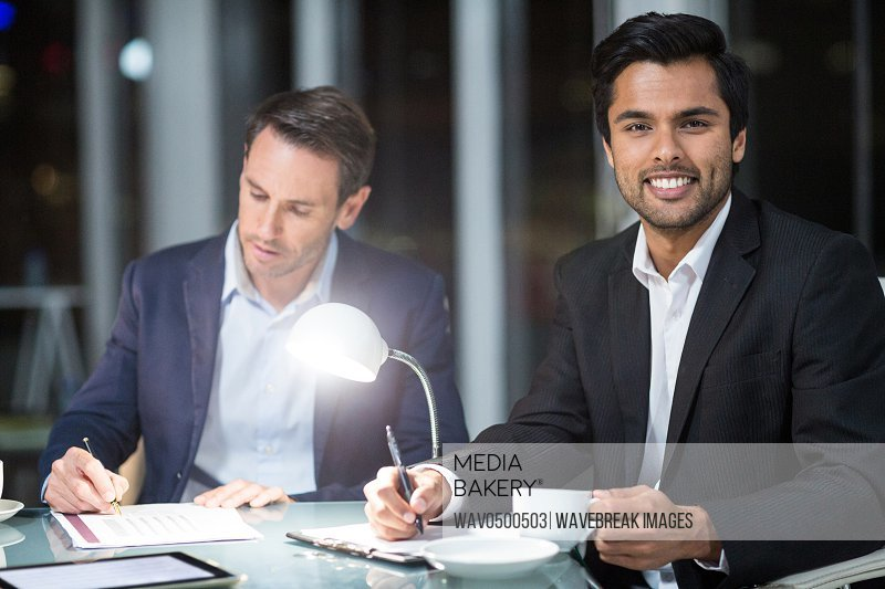 Businessman smiling at camera while colleague writing on paper in the office
