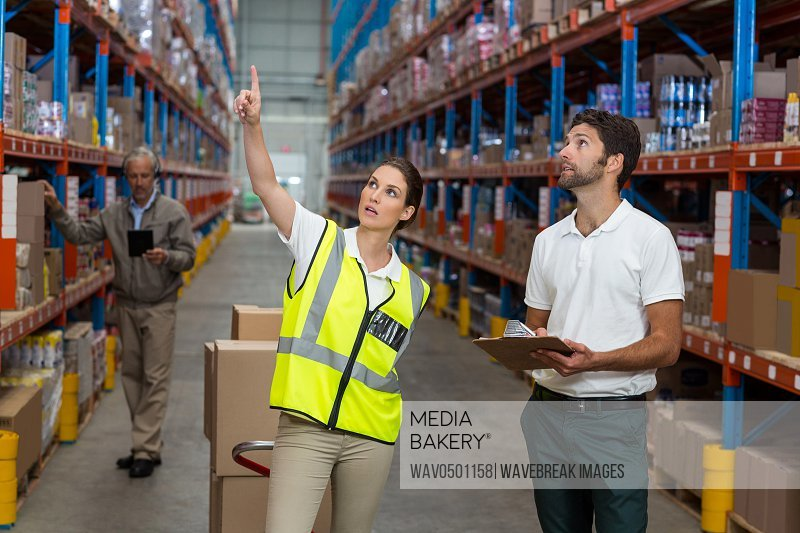 Male and female worker checking inventory in warehouse