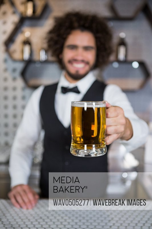Portrait of smiling bartender holding glass of beer in bar counter at bar