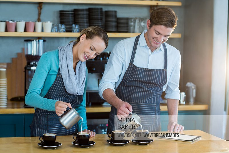 Smiling waiter and waitress making cup of coffee at counter in cafe
