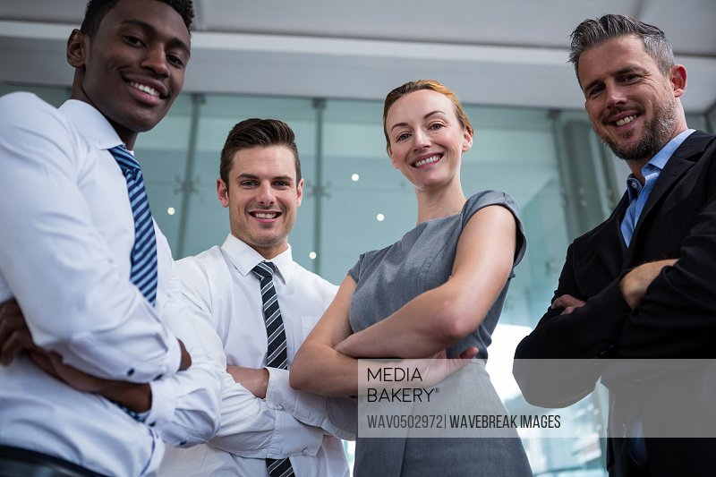 Portrait of happy businesspeople standing with arms crossed in office