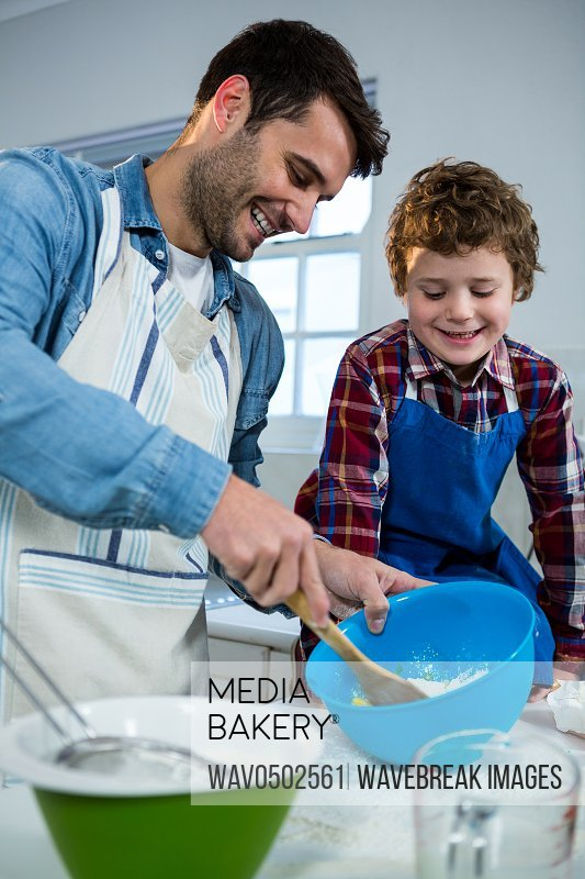 Father teaching his son how to make cupcake in the kitchen