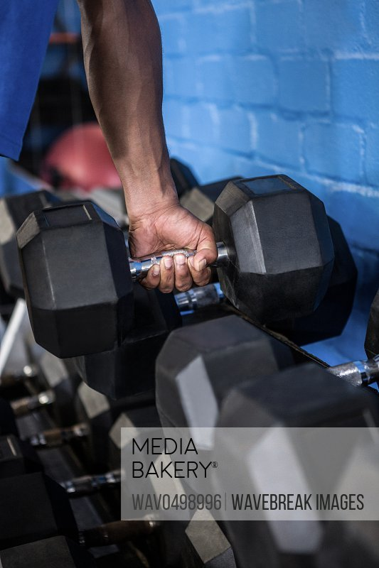 Cropped image of man exercising with dumbbell in gym